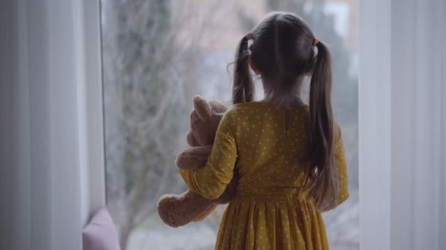 Back view of little Caucasian girl hugging teddy bear and looking out the window. Brunette kid spending day at home with toy. Leisure, lifestyle, childhood.