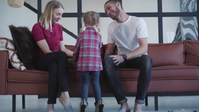 Back view of little Caucasian girl walking in high-heels to sofa. Young smiling man and woman sitting on couch and admiring daughter enjoying weekends at home. Lifestyle, leisure, childhood.