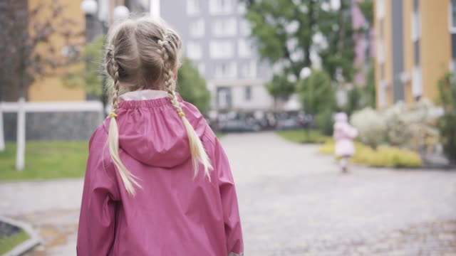 Back view of little girl with pigtails in pink waterproof coat walking outdoors. Blond pretty Caucasian child resting outdoors on spring or summer day. Lifestyle, leisure, relaxation. Back view of little girl with pigtails in pink waterproof coat walking outdoors. Blond pretty Caucasian child resting outdoors on spring or summer day. Lifestyle, leisure, relaxation. pigtails stock videos & royalty-free footage