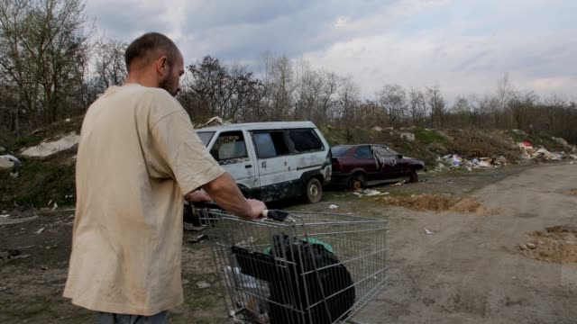 Back view of male pushing shopping cart at landfill Back view of homeless male walking at landfill site with garbage and old abandoned cars, pushing cart with plastic bags. Homelessness and social issues concept. Steadicam shot. homeless person stock videos & royalty-free footage
