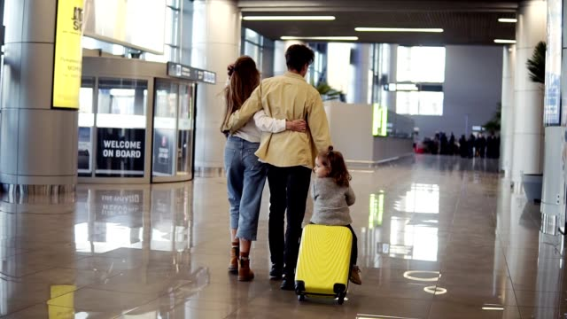 Back view of modern caucasian family - mother, father, daughter - walking the airport hall and riding their daughter on suitcase before the departure to the vacation. Slow motion video