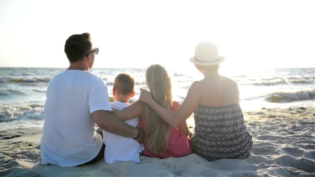 Back View of Mother, Father, Son and Daughter Hugging on the Beach near the Sea video