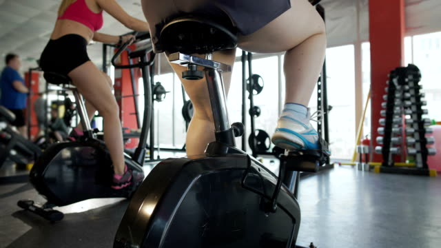 Back view of overweight woman pedalling on stationary bike in the sports club video