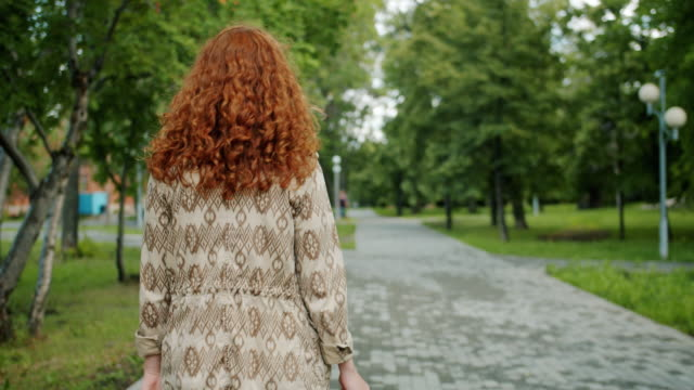 Back view of pretty redhead girl walking in park alone turning to camera smiling Back view of pretty redhead girl student walking in green park alone turning to camera smiling. Beautiful people, adolescence and modern lifestyle concept. redhead stock videos & royalty-free footage
