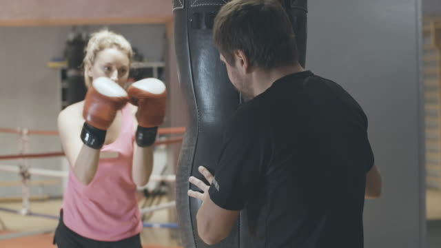 back view of professional coach holding punching bag and endorsing young blond woman punching equipment. personal trainer training female self-defense or boxing in gym. cinema 4k prores hq. - {{relatedsearchurl(carousel.phrase)}} video stock e b–roll