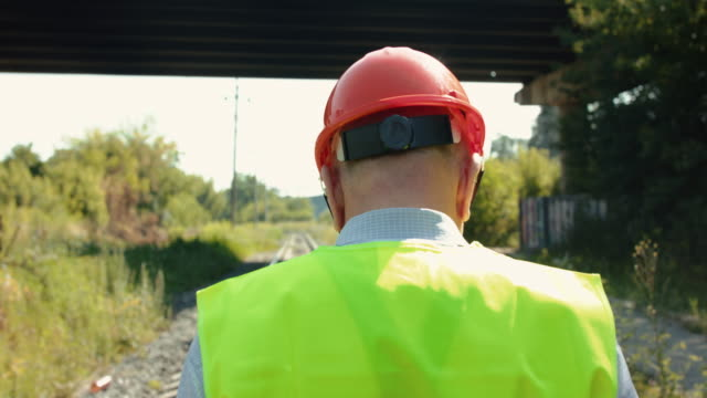 Back view of railroader in uniform walking on the railway video