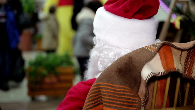 Back view of Santa Claus looking at busy passers-by in Back view of Santa Claus looking at busy passers-by in crowded trade center shopping mall stock videos & royalty-free footage