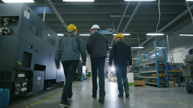 Back view of senior engineer and two workers are walking with papers through the factory space.