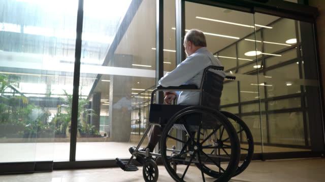 ガラスのドアを通して見ている老人ホームで車椅子に乗っているシニアの男性の背面図 - 老人ホーム点の映像素材/bロール