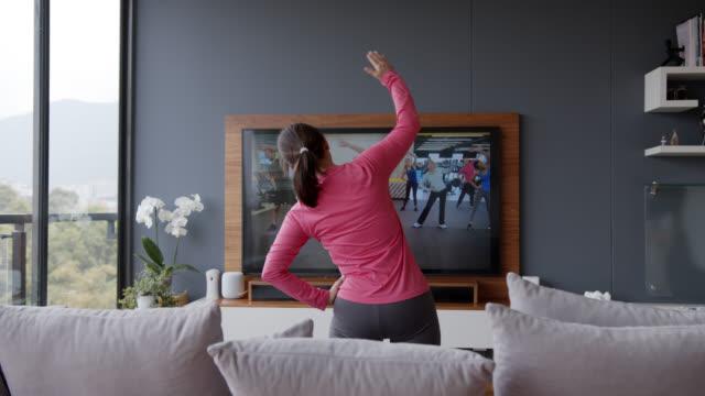 vista posteriore della donna anziana che segue una lezione di stretching online guardando lo schermo della tv - esercizio fisico video stock e b–roll