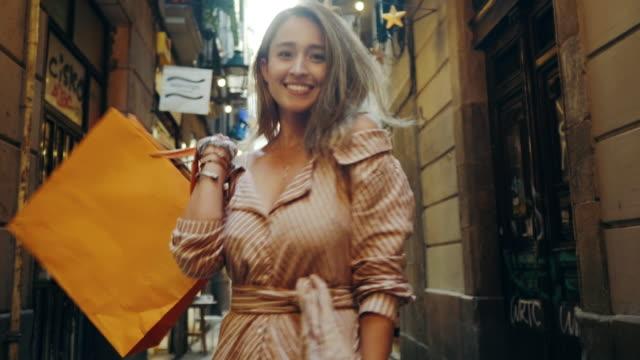 vídeos y material grabado en eventos de stock de vista trasera de la mujer de compras caminando por la calle de la ciudad. chica turística buscando cámara - shopping bags