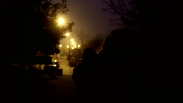 back view of single mother holds her little son in hand and walking in the night road. woman immigrates with little boy - fuggitivo video stock e b–roll