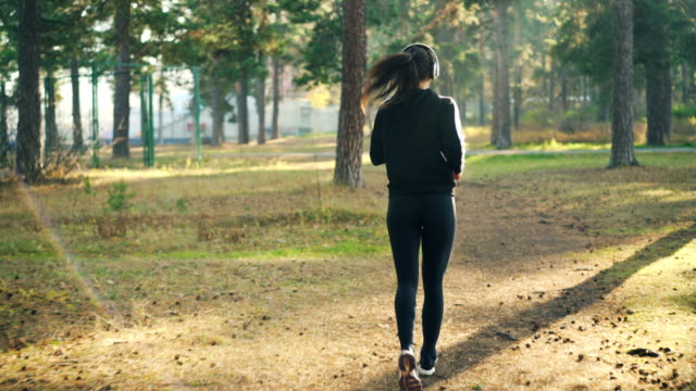 Back view of slender young woman in sportswear jogging in park and wearing headphones listening to music training alone. Slenderness, sports and nature concept. Back view of slender young woman in sportswear jogging in park and wearing headphones listening to music training alone. Slenderness, sports and autumn nature concept. athleticism stock videos & royalty-free footage