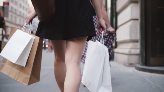 stockvideo's en b-roll-footage met achteraanzicht van succesvolle jonge meisje verslaafd aan winkelen vervoeren zakken in beide handen wandelen langs de straat slowmotion - tas