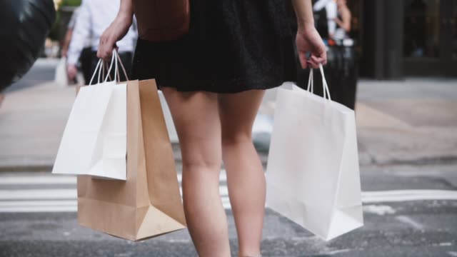 back view of successful young woman in short black dress carrying shopping bags while crossing the street slow motion - vendita al dettaglio video stock e b–roll