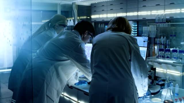 シニアや問題解決に取り組んでいる若手研究者のチームの背面します。彼らはコンピューター上の情報を探しています。彼らの実験室は超近代的です。 - 研究所点の映像素材/bロール