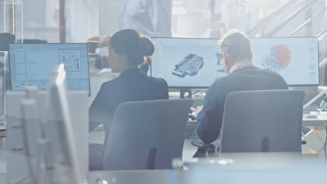 vidéos et rushes de vue de dos de l'équipe d'ingénieurs de technologie travaillant sur des ordinateurs de bureau dans le bureau lumineux. écrans afficher les logiciels ide/cad, implémentation de machine learning, réseau neuronal et cloud computing - science et technologie