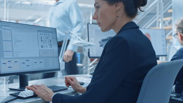 明るいオフィスのデスクトップコンピュータで作業している技術エンジニアのチームのバックビュー。画面には、ide/cad ソフトウェア、機械学習の実装、ニューラルネットワーキング、およ� - 研究所点の映像素材/bロール