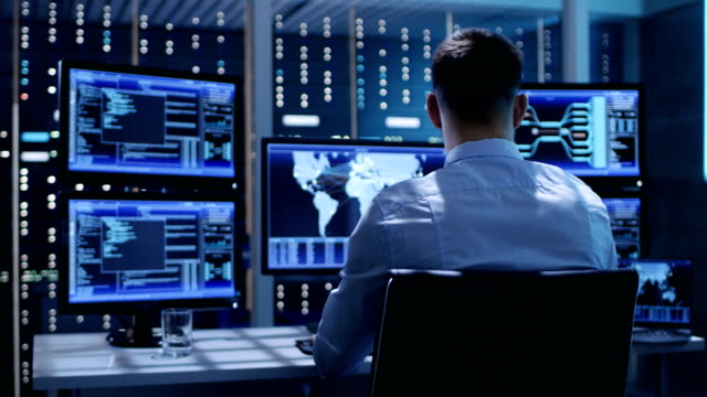 Back View of Technical Controller/ Operator Working at His Workstation with Multiple Displays. Possible Power Plant/ Airport Dispetcher/ Dam Worker/ Government Surveillance/ Space Program Back View of Technical Controller/ Operator Working at His Workstation with Multiple Displays. Possible Power Plant/ Airport Dispetcher/ Dam Worker/ Government Surveillance/ Space Program. Shot on RED EPIC-W 8K Helium Cinema Camera. cybersecurity stock videos & royalty-free footage