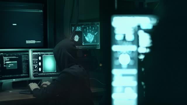 コンピューターでの作業とウイルス データを政府のインフラストラクチャのサーバーに感染させる 10 代のハッカーの背面します。彼の隠れ家は、多くのモニターの周りに暗いです。 - なりすまし犯罪点の映像素材/bロール
