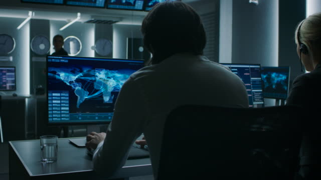 back view of the cyber security dispatchers working on personal computer showing traffic data flow in the system control room full of special intelligence agents. - quartiere generale video stock e b–roll