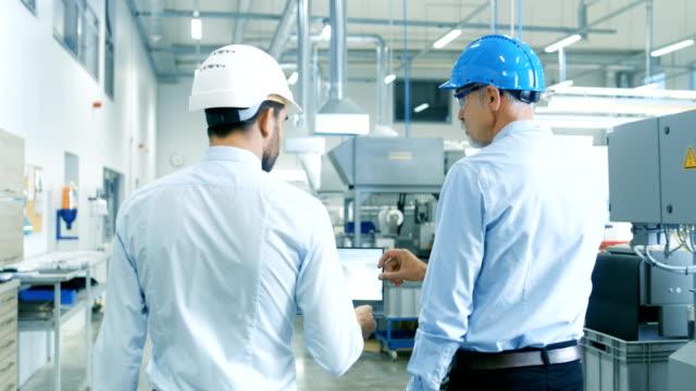 vidéos et rushes de arrière de la tête du projet détient portable et discuter des détails de produit avec l'ingénieur en chef tandis qu'ils marcher à travers l'usine moderne. vue arrière moyenne shot. - électricité
