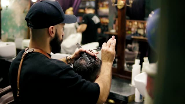 Back view of the stylish bearded barber in a black cap wearing leather apron performing a haircut with scissors holding a hair brush in his hands video