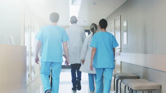 vidéos et rushes de arrière de l'équipe de médecins, infirmières et assistants marchant dans le couloir de l'hôpital. personnel médical professionnel travaillant, sauver des vies. mouvement lent. - couloir