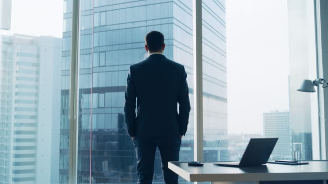 Back View of the Thoughtful Businessman wearing a Suit Standing in His Office, Hands in Pockets and Contemplating Next Big Business Deal, Looking out of the Window. Big City Business District Panoramic Window View.
