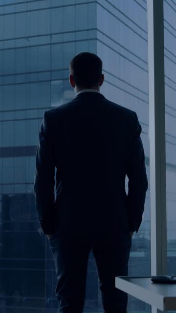 rückblick auf den nachdenklichen geschäftsmann, der einen anzug trägt, der in seinem büro steht, über den nächsten big business deal nachdenkt, aus dem fenster schaut. videomaterial mit vertikaler bildschirmausrichtung 9:16 - generaldirektor oberes management stock-videos und b-roll-filmmaterial