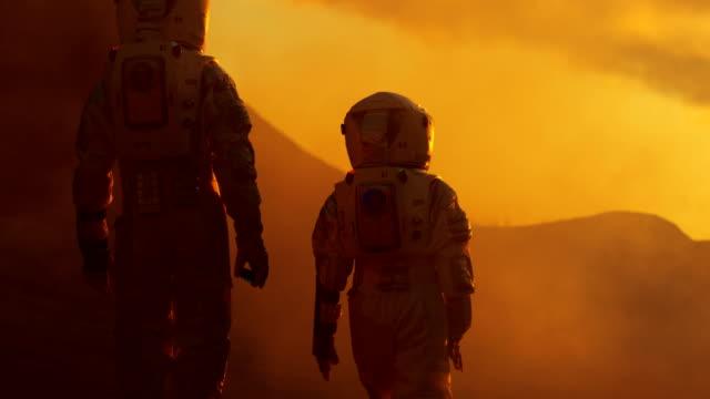 rückansicht der beiden astronauten raumanzüge tragen zu fuß erforschen mars / red planet. raumfahrt, erforschung und kolonisierung konzept. - raumanzug stock-videos und b-roll-filmmaterial