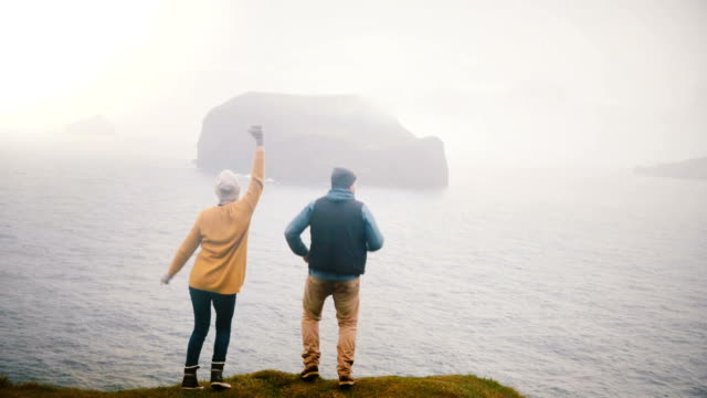 Back view of the young happy couple are standing on the shore of a sea and jumping of joy, hugging in iceland.