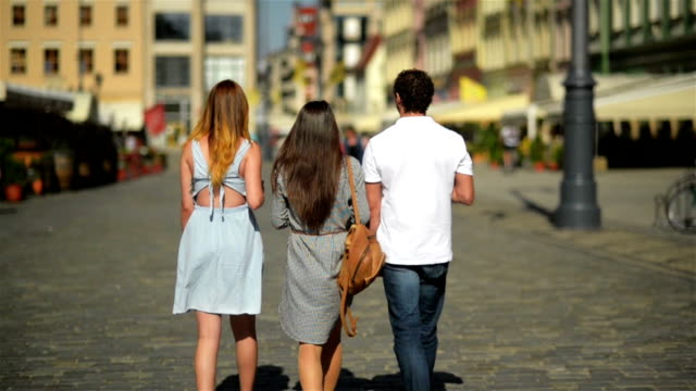 Back View of Three Friends Drinking Coffee and Walking around the City. Two Girls Wearing Sunglasses and Short Dresses and Handsome Boy in White Shirt and Jeans Spending Time Together video