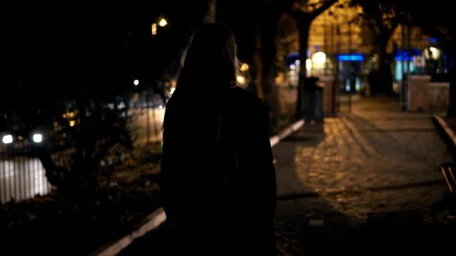stockvideo's en b-roll-footage met achteraanzicht van toeristische vrouw met rugzak wandelen door het donkere park in de buurt van de weg laat 's nachts alleen - vrouw verdrietig