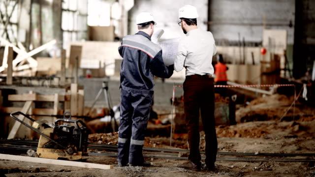 Vista posterior de dos hombres juntos de pie en el área de la construcción y mirando los planos de la futura estructura. Capataz en camiseta y pantalón está negociando con el trabajador sobre los detalles del edificio-para arriba - vídeo