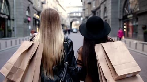 vidéos et rushes de vue arrière de deux femmes à pied avec les sacs à provisions - faire les courses