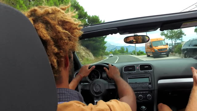 Back view of two young male friends driving in convertible on coastal highway video