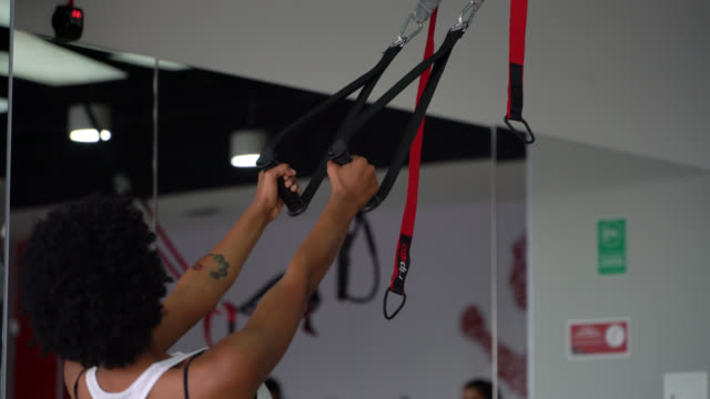 Back view of unrecognizable black woman working out with suspension straps at the gym