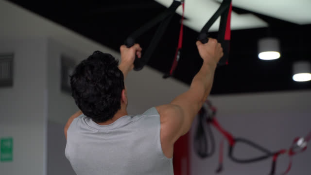 Back view of unrecognizable man working out with suspension straps at the gym