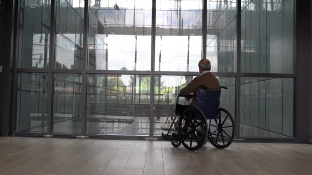 Back view of unrecognizable senior man on wheelchair at a retirement home Back view of unrecognizable senior man on wheelchair at a retirement home - Healthcare concepts wheelchair stock videos & royalty-free footage