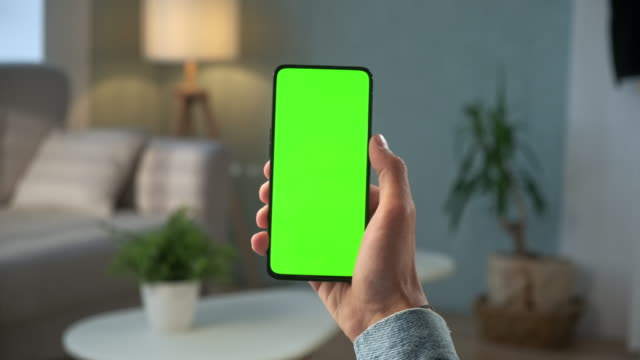 Back View of Woman at Modern Room Sitting on a Chair Using Phone With Green Mock-up Screen Chroma Key Without Track Points Surfing Internet Watching Content Videos Blogs. Double Swipe Up