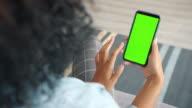 istock Back view of woman brunette using green screen smartphone touching screen 1201655348