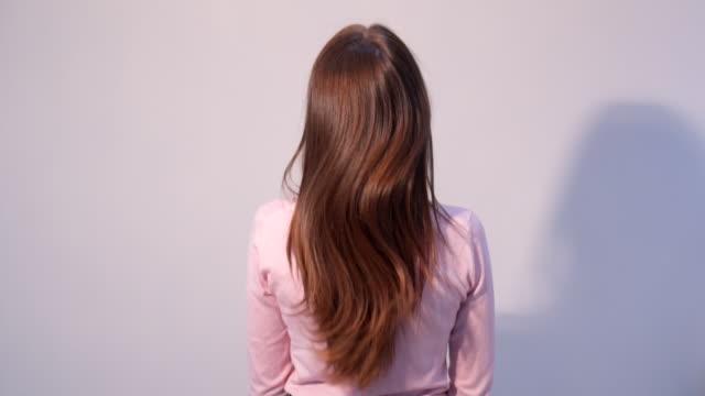 vidéos et rushes de vue arrière de femme posant avec le cheveu après le redressage dans le salon de beauté - vue partielle