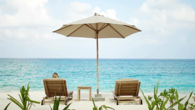 vídeos de stock, filmes e b-roll de vista traseira da mulher tomando banho de sol na praia, ela está mentindo na cadeira deck com uma vista linda do mar. idílico paraíso - férias na praia