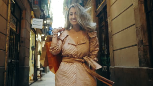 back view of woman walking with shopping bags. smiling girl flirting on camera - borsa della spesa video stock e b–roll
