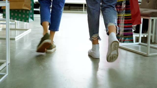 stockvideo's en b-roll-footage met achteraanzicht van vrouwen benen gaan langzaam door ruime winkel. meisjes zijn het dragen van jeans en trainers en dragen kleurrijke papieren zakken. - running shoes