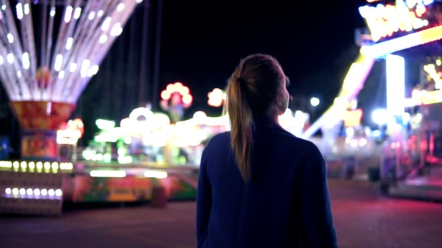 Back view of young attractive girl with ponytail walking forward then turning around smiling and looking at camera hanging out in amusement park with attractions background. Slowmotion shot video