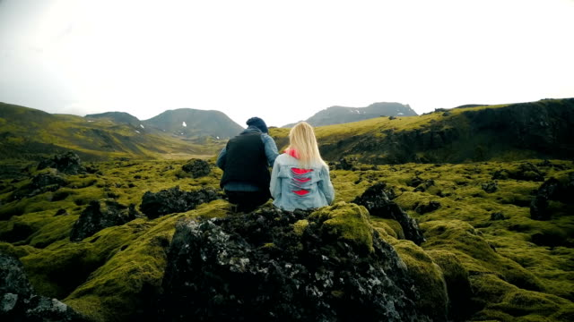 Back view of young beautiful couple sitting on the rock and enjoying the scenic landscape of the lava fields in Iceland video