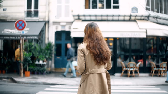Back view of young beautiful woman crossing the road in Paris, France. Stylish female in cloak walking on the street video