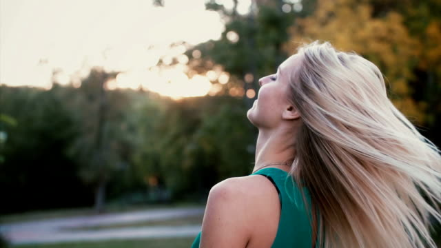 Back view of young blonde woman in park on sunset. Girl moving her head and hair waving on the wind. Slow motion Back view of young blonde woman in park on sunset. Girl moving her head and hair waving on the wind. Female having rest outside in summer evening. Slow motion. expressionism stock videos & royalty-free footage